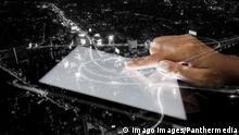Hand mit Tablet und Stadt auf nächtlichem Hintergrund
