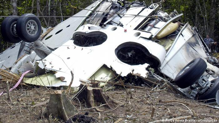 Parte da fuselagem do avião. É possível observar o trem de pouso aberto, com as rodas para cima