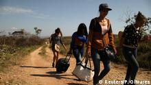 Venezuelan migrants walk along a trail into Brazil, in the border city of Pacaraima, Brazil, April 11, 2019. Picture taken April 11, 2019. REUTERS/Pilar Olivares