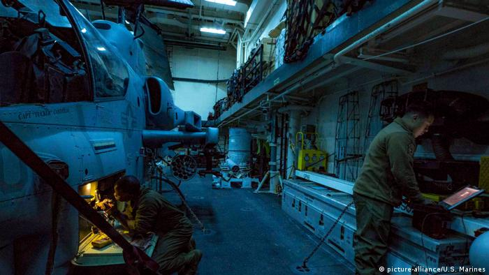Technicians troubleshoot a night targeting system on an AH-1W Cobra attack helicopter on the flight deck of the USS Arlington
