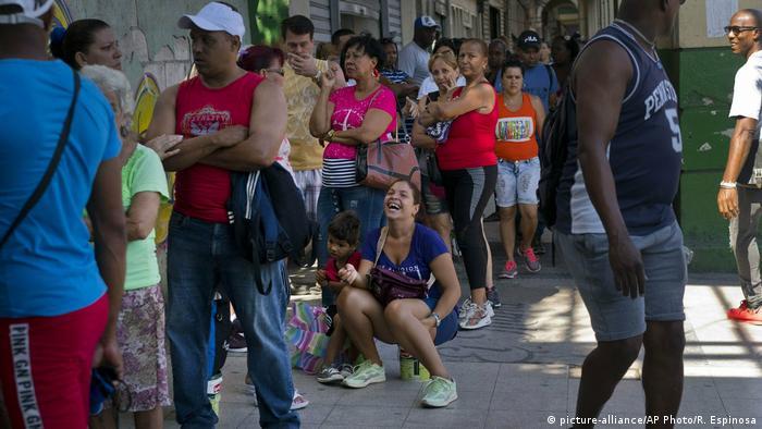 Moça sentada sobre lata sorri numa fila de supermercado em Havana, Cuba