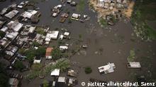 dpatopbilder - 11.05.2019, Paraguay, Asuncion: Die Luftaufnahme zeigt das überschwemmte Viertel Ricardo Brugada, hauptsächlich als La Chacarita bekannt, in der Hauptstadt von Paraguay. Nach heftigem Regen sind in Paraguay zahlreiche Dörfer, Felder und Straßen überschwemmt worden. Im Süden des südamerikanischen Landes erreichte der Paraguay-Fluss an vielen Stellen kritische Pegelstände. Foto: Jorge Saenz/AP/dpa +++ dpa-Bildfunk +++ |