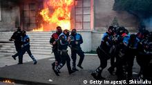 A petrol bomb explodes behind police officers during an anti-government protest called by the opposition on May 11, 2019 in Tirana. (Photo by GENT SHKULLAKU / AFP) (Photo credit should read GENT SHKULLAKU/AFP/Getty Images)