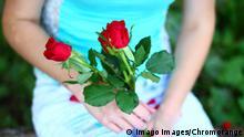 Frau mit Blumenstrauß Muttertag Rote Rosen (Imago images/Chromorange)