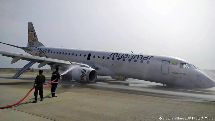 Firefighters work with hose on a plane of Myanmar National Airline (MNA) after an accident at Mandalay International airport Sunday, May 12, 2019, in Mandalay, Myanmar.