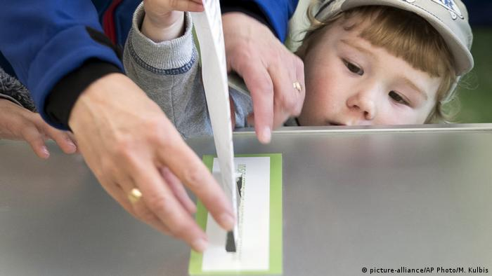 A woman and child cast her ballot during the first round of voting in Lithuania (picture-alliance/AP Photo/M. Kulbis)