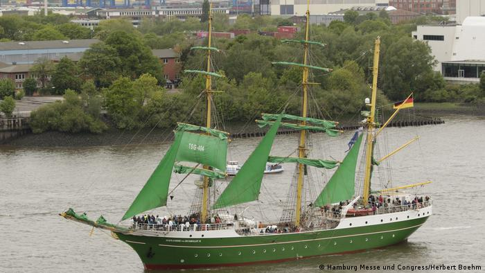 A tall ship with green bow and sails