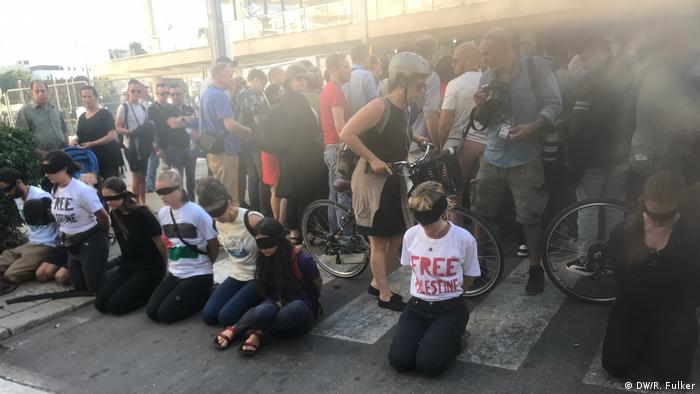 Protesters kneel wearing blindfolds and T-shirts that read 'Free Palestine' in front of the press entry to the ESC red carpet reception in Tel Aviv