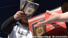 ARCHIV - ARCHIV - 14.04.2012, Niedersachsen, Hannover: EinIslamist verteilt in der Innenstadt kostenlose Koran-Exemplare an Passanten. (zu dpa LKA vermisst Unterstützung vonEltern radikalisierter Jugendlicher vom 29.06.2018) Foto: Julian Stratenschulte/dpa +++ dpa-Bildfunk +++ | Verwendung weltweit