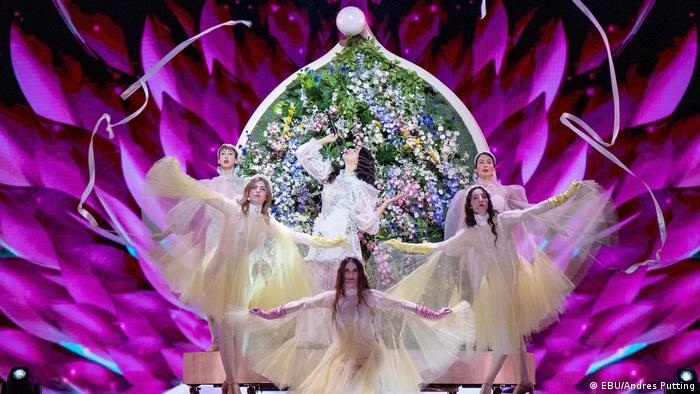 A singer and five ballet dancers in diaphonous gowns backdropped by floral arrangements (EBU/Andres Putting)