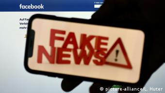 Надпись fake news на экране смартфона на фоне логотипа Facebook