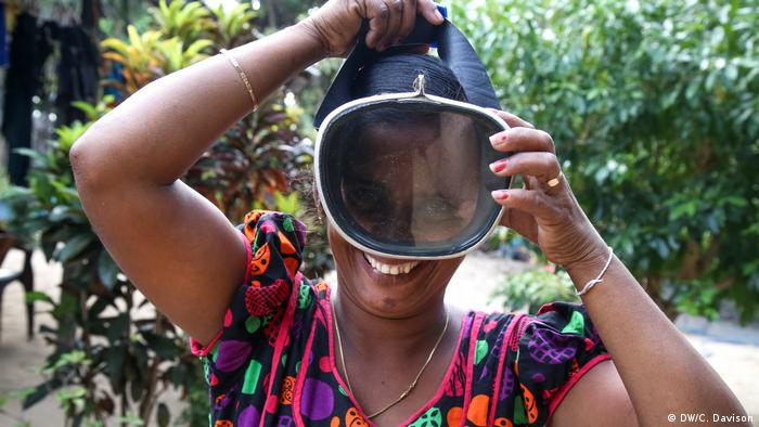 A smiling woman puts a scuba diving mask over her head