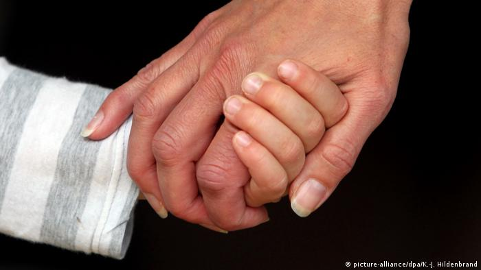 A child holding on to the hand of a parent