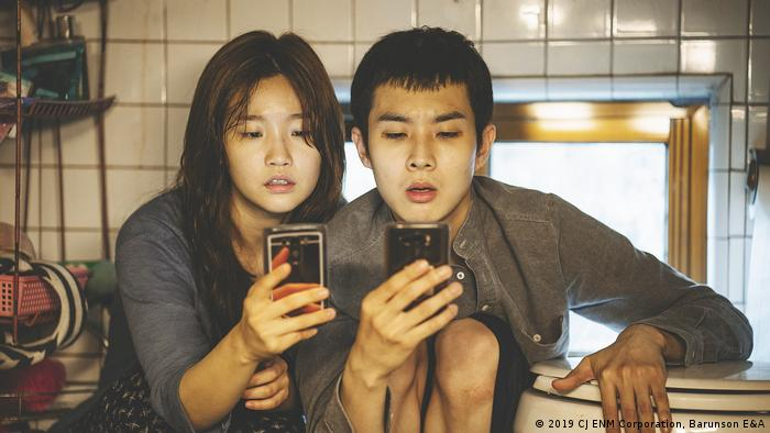 Film still Gisaengchung: a young Asian woman and Man stare into their smartphones in a kitchen (2019 CJ ENM Corporation, Barunson E&A)