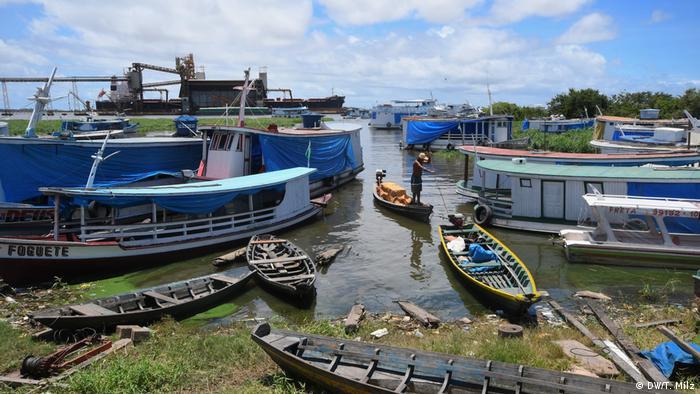 Pescador em bote movido a motor transita em meio a outros barcos às margens do rio próximo à aldeia Açaizal, da etnia munduruku. Ao fundo, vê-se a estação de carregamento de soja da empresa alimentícia Cargill