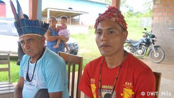 De camiseta vermelha, colar de madeira e chapéu adornado com penas vermelhas, o cacique Josenildo Munduruku dá entrevista sentado em cadeira de madeira. No lado esquerdo da foto, um outro membro da etnia munduruku, mais velho, com cocar de penas azuis e camiseta azul-clara. Ao fundo, vê-se uma motoicleta e uma mulher carregando uma menina de colo, à frente de um carro branco