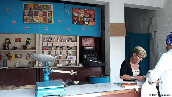 A clerk engaged in a transaction with a customer in a Cuban store