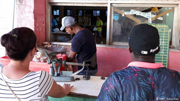 Cubans watch as a man portions out meat behind a counter