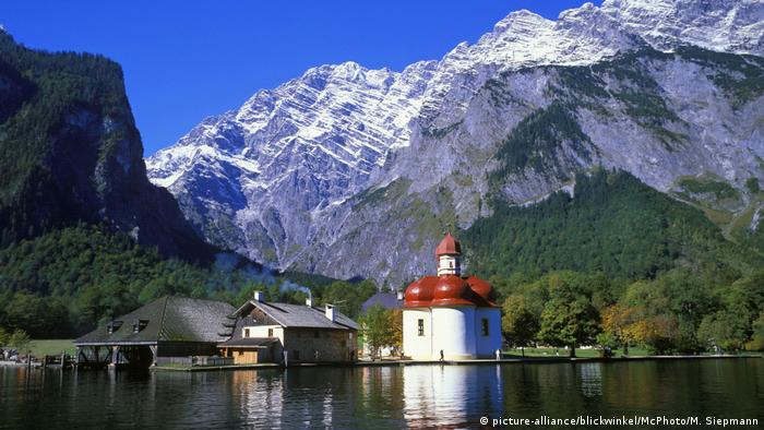 View across Lake Königsee in Bavaria at a church and high Alpine peaks