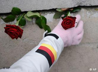 A hand places a rose on a section of the Wall