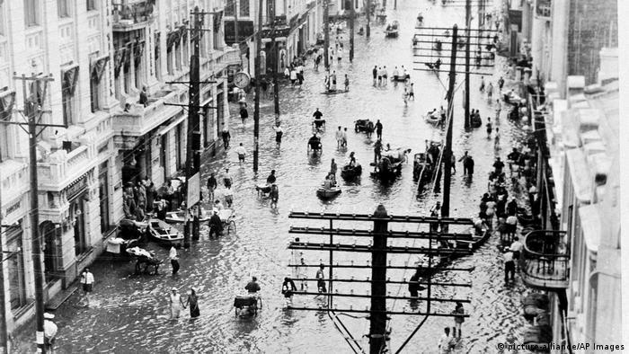 Foto em preto e branco mostra rua alagada, com pessoas andando em meio à água e em alguns barcos pequenos.