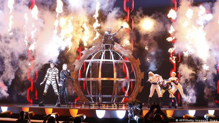 Singers and dancers in bizarre costumes on a smokey, stage with an iron cage in the middle (AFP/Getty Images/J. Guez)