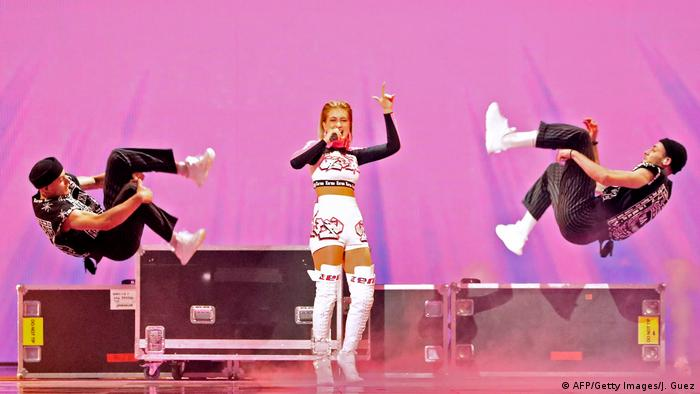 The singer dances while to either side, two male dancers do a backflip (AFP/Getty Images/J. Guez)