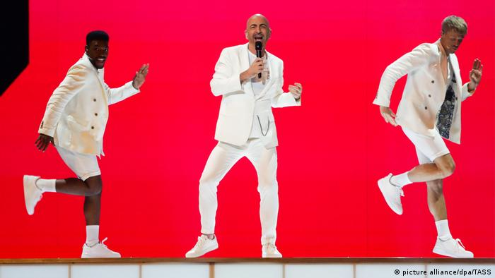 Man with a microphone flanked by two singers in white before a stark, crimson red background (picture alliance/dpa/TASS)