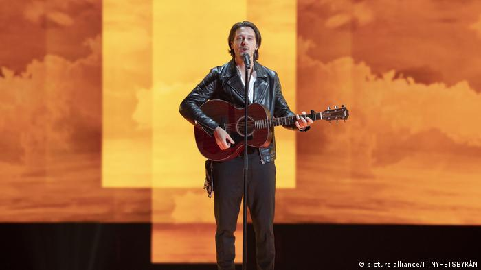 Eurovision Song Contest 2019 | Man with guitar before an amber, cloudy background (picture-alliance/TT NYHETSBYRÅN)
