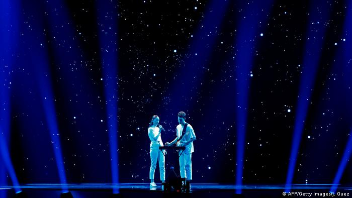 Female singer and male guitarist in white on a stage set suggesting a starry night (AFP/Getty Images/J. Guez)