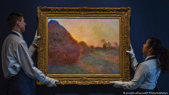 Two auction helpers hold up a Monet painting of haystavks (picture-alliance/AP Photo/Sotheby's)