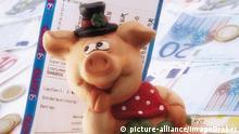 Glücksschwein mit Lottoschein auf Euroscheinen