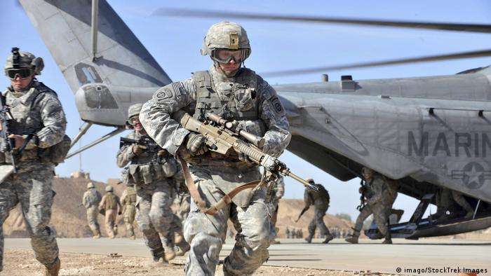A U.S. Army soldier runs over to provide security after unloading from a CH-53 Sea Stallion helicopter