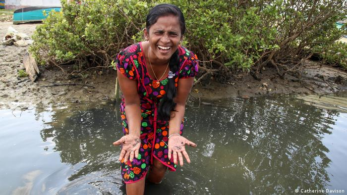 A woman in a colorful dress standing in shallow water holds her outspread, muddy hands to the camera and smiles
