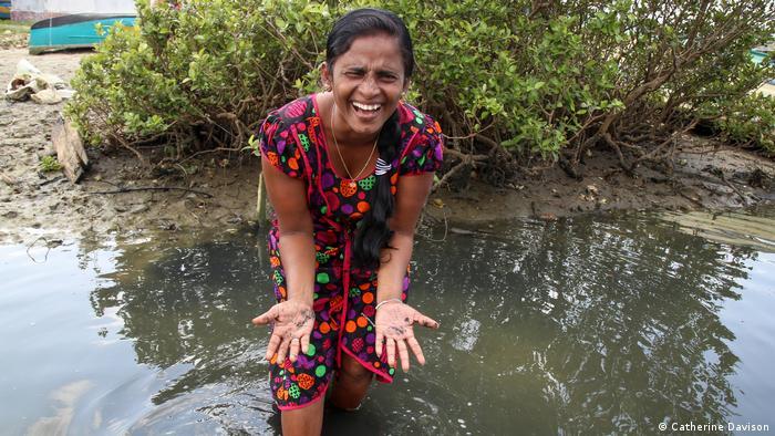 Eine Frau in Sri Lanka in einem farbenfrohen Kleid steht im flachen Wasser. Sie hält lachend ihre ausgestreckten, schlammigen Hände in die Kamera.