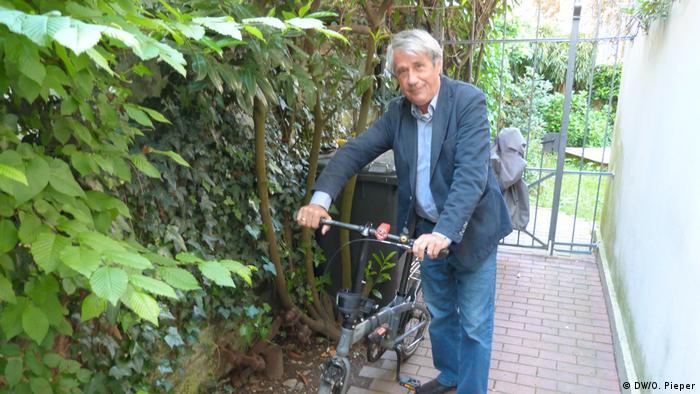 O especialista em trânsito Heiner Monheim empurra sua bicicleta dobrável