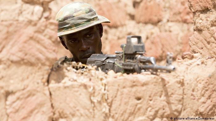 A soldier holds a gun