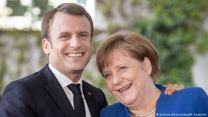 Emmanuel Macron and Angela Merkel share a moment