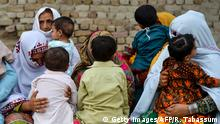 In this image taken on May 8, 2019, Pakistani women hold their HIV infected children as they gather at a house at Wasayo village in Rato Dero in the district of Larkana of the southern Sindh province. - Parents nervously watch over their children as they jostle in line to be tested for HIV in a village near Pakistans Larkana amid a sudden outbreak among its young who have allegedly been infected by a doctor using a contaminated syringe. (Photo by RIZWAN TABASSUM / AFP) / TO GO WITH: Pakistan-health-HIV-children, SCENE by Ashraf KHAN (Photo credit should read RIZWAN TABASSUM/AFP/Getty Images)