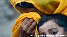 In this image taken on May 8, 2019, a Pakistani woman cries in her scarf as she holds her HIV infected child outside a house at Wasayo village in Rato Dero in the district of Larkana of the southern Sindh province. - Parents nervously watch over their children as they jostle in line to be tested for HIV in a village near Pakistans Larkana amid a sudden outbreak among its young who have allegedly been infected by a doctor using a contaminated syringe. (Photo by RIZWAN TABASSUM / AFP) / TO GO WITH: Pakistan-health-HIV-children, SCENE by Ashraf KHAN (Photo credit should read RIZWAN TABASSUM/AFP/Getty Images)