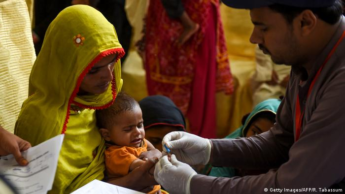 A Pakistani paramedic takes blood sample from a baby for a HIV test in Larkana district