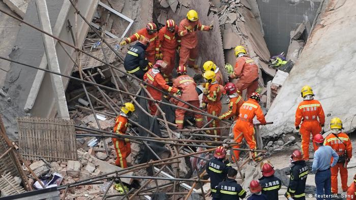 Rescue workers extract a victim from the destroyed structure in Shanghai