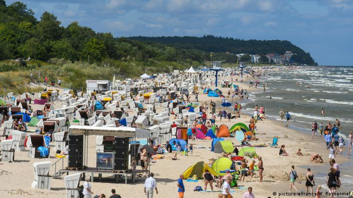 Busy Baltic Sea beach with bathers lying under beach tens and parasols