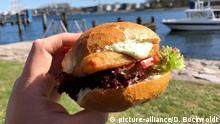 Ein Mann am 01.04.2019 am Fluss Trave an der Mündung zur Ostsee ein Fischbrötchen mit Backfisch, Salat und Remoulade. Foto: Daniel Bockwoldt | Verwendung weltweit