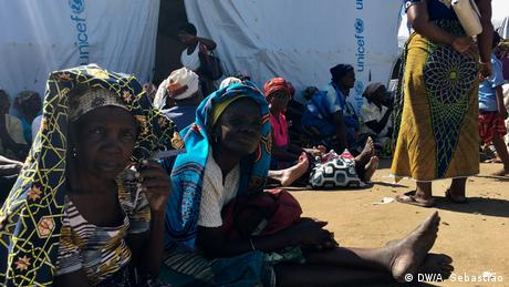Women sit outside a UNICEF tent in Mozambique. (DW/A. Sebastião)