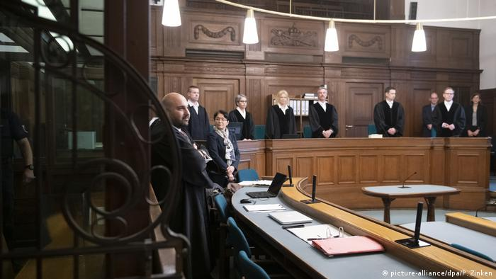 Magomed-Ali C.'s lawyers stand waiting for their client in a Berlin court room