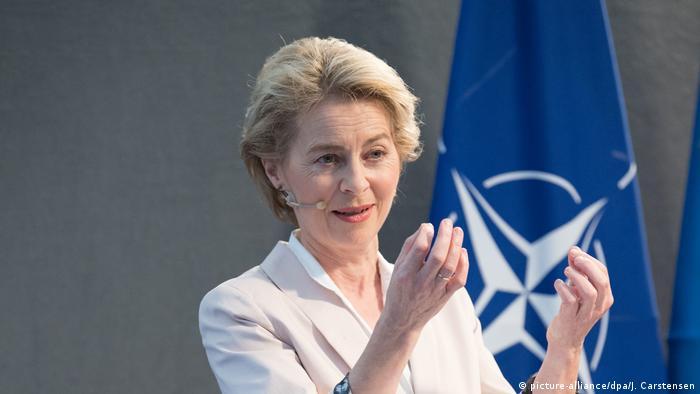 Ursula von der Leyen in front of NATO flag