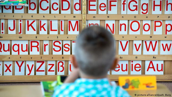 A child sits in front of a board with letters on it