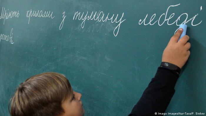 Мальчик пишет на доске предложение на украинском языке