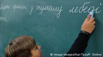 Школьник пишет предложение мелом на доске